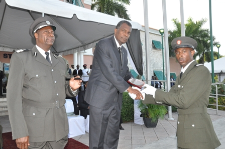 AWARD OF EXCELLENCE – Devaughn Anderson accepts the Award of Excellence honour from the Hon. Frederick Mitchell, Minister of Foreign Affairs and Immigration during Graduation Ceremony for Class of 2014 – Squad A at Freeport, Grand Bahama on Thursday.  Left is Mr. Hubert E. Ferguson, Assistant Director of Immigration.
